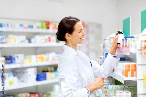 Plexiglas Apotheek medicine, pharmaceutics, healthcare and people concept - happy female apothecary taking drug from shelf at pharmacy