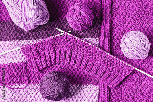Balls of wool  and unfinished knitting in violet tones, flat lay