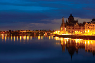 Hungarian Parliament building at night, reflected in still Danube water