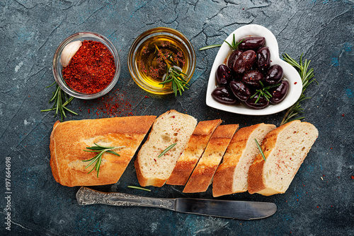 Fresh ciabatta with olive oil and olives on dark background. top view