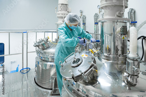 Leinwanddruck Bild Pharmaceutical factory woman worker in protective clothing operating production line in sterile environment