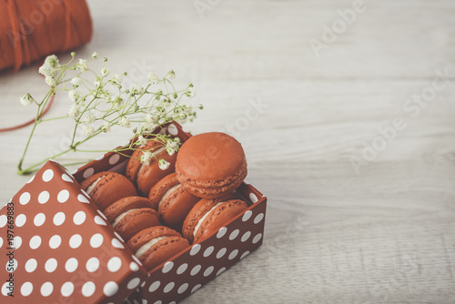 Fotobehang Macarons Stylish red dots box with tasty macarons on wooden background. Minimalist concept of style and french chic, copy space and selective focus.
