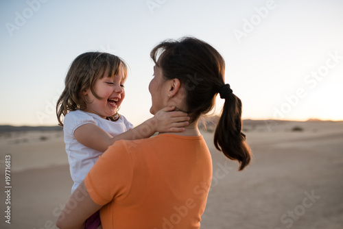 Laughing girl hugging with mother on sand dune during sunset