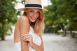 Happy delighted woman has pleasant appealing appearance, wears summer hat and white dress, has stroll on street, enjoys vacations or day off. Pretty young green eyed glad female model poses outdoor