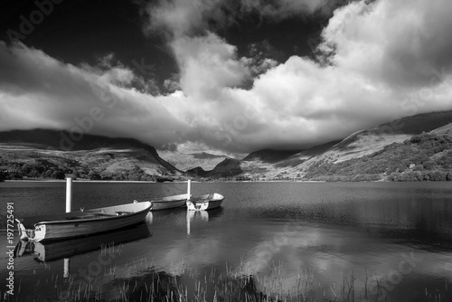 Plexiglas Pier Black and white Landscape image of rowing boats on Llyn Nantlle in Snowdonia at sunset