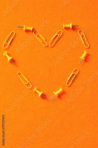 Yellow paperclips and push pins on an orange background