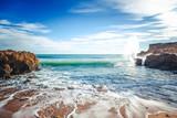 Beautiful coast of the ocean, Algarve, Portugal. Waves break against the rocks in the sun