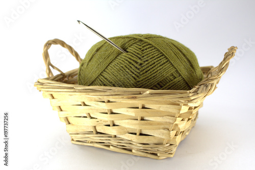 Green tangle of natural wool for needlework with a crocheted crochet stuck in it in a wicker basket on a white background close-up