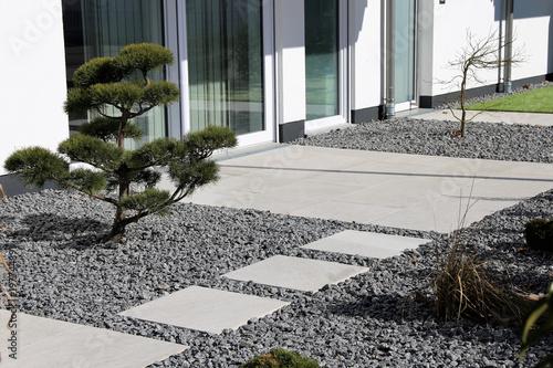 Kleiner Ziergarten mit grauen Terrassenplatten