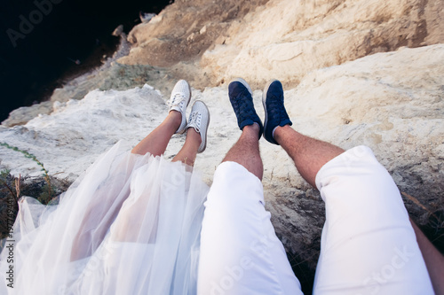 Сouple in love sits on a high cliff near the sea, hanging their legs down. Guy in white breeches and blue sneakers, a girl in net moccasins and an airy white skirt. Look at her feet POV. - 197749441