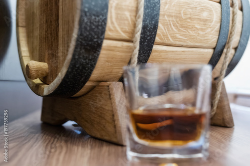 A small wooden oak barrel for home production and a stack of whiskey aged in it