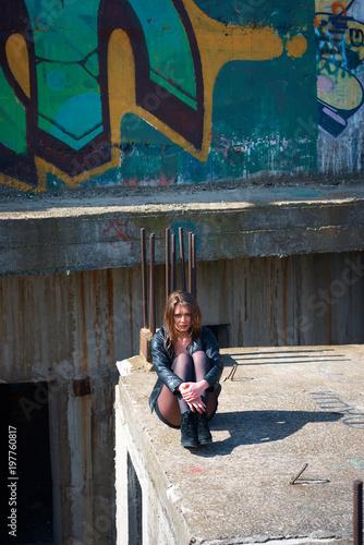 Fotobehang Graffiti Young slim brunette on a ruins of abandoned building