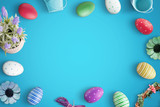 Easter colorful eggs on blue desk. Copy space in the middle for text. Top view.