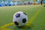 Soccer ball on a corner kick line on an artificial green grass