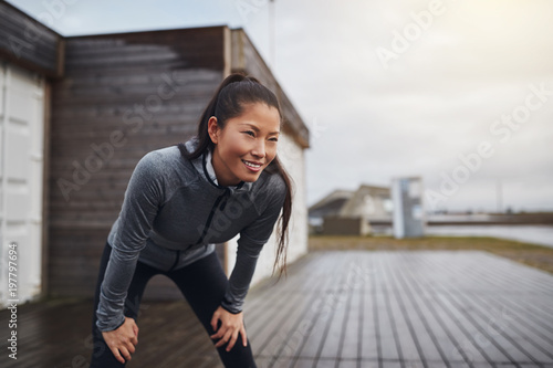 Aluminium Hardlopen Smiling young Asian woman taking a break while out jogging