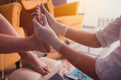 Foto op Plexiglas Spa Close up worker hands taking care of client leg while holding it indoor. Profession concept