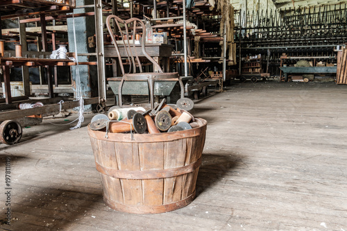 Foto op Canvas Oude verlaten gebouwen Bucket full of silk and thread spools on an old factory floor