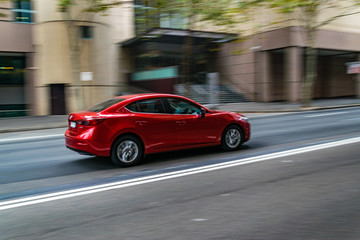 Red car in motion on the road, Sydney, Australia. Car moving on the road, blurred buildings in background.