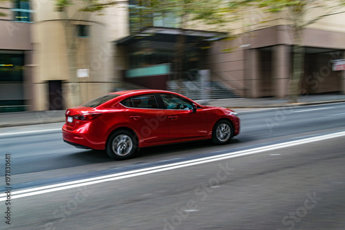 Foto op Aluminium Sydney Red car in motion on the road, Sydney, Australia. Car moving on the road, blurred buildings in background.