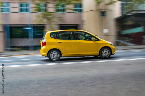 Yellow car in motion on the road, Sydney, Australia. Car moving on the road, blurred buildings in background.