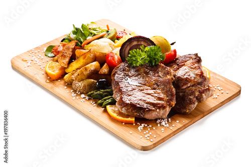 Foto op Plexiglas Steakhouse Roast steak with vegetables on cutting board