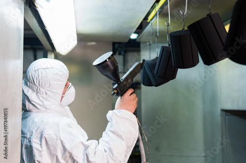 Lakierowanie proszkowe części metalowych. Mężczyzna w stroju ochronnym rozpyla farbę w proszku z pistoletu na metalowych produktach