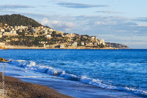 Foto op Plexiglas Nice NICE, FRANCE, on March 6, 2018. The sunset sun lights waves of a sea surf in a picturesque bay and buildings on the mountain on its coast