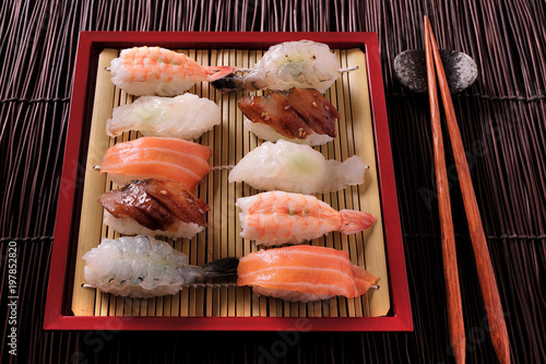 Foto op Plexiglas Sushi bar Japanese sushi various assortment red bamboo tray chopsticks