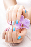 beautiful colored manicure with orchid, candle and towel on the white wooden table.