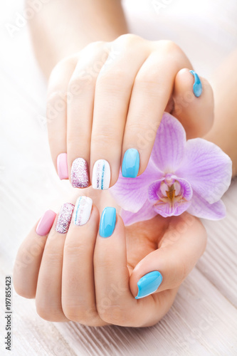 beautiful colored manicure with orchid, candle and towel on the white wooden table. - 197855423