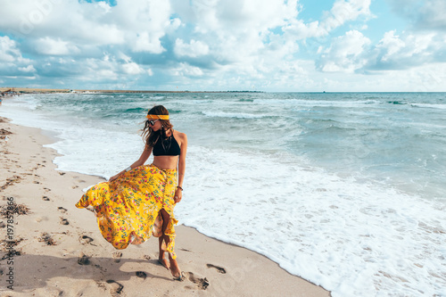 Boho girl walking on the beach