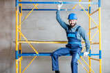 Builder in blue working uniform sitting on the scaffolding indoors - 197858264