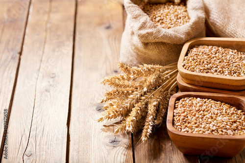 grains and wheat ears on a wooden table - 197871658
