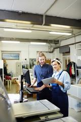 People in printshop controlling work before final printing