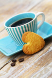 Heart shaped crunchy cookie leaning against blue cup of coffee on rustic wooden surface