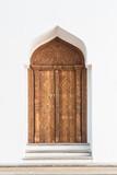 Old Arabian door in white wall in Morocco.