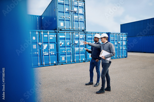 Dwóch inżynierów śledzących zapasy wysyłkowe w kontenerze