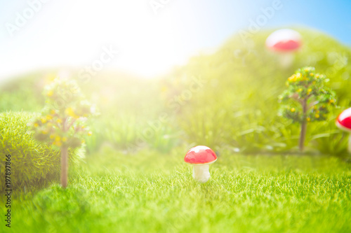 Foto op Plexiglas Lime groen Toy Landscape. Sunset on the plastic green field with plastic grass, mushrooms and trees. Fake grass. Macro