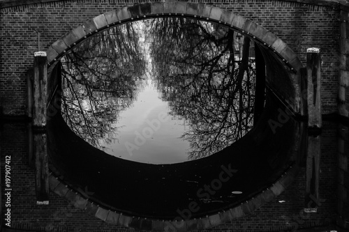 Foto op Aluminium Amsterdam water canals in Amsterdam with a bridge in the middle and traditional architecture black and white