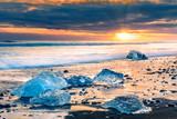 Drifting ice blocks on Diamond beach, at sunset, in Jokulsarlon, Iceland - 197915493