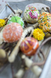 Homemade handmade painted Easter eggs on birch branches on grey wooden tray, traditional hnadcraft eggs