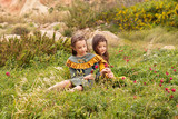 two girls in retro vintage dresses picking flowers on a meadow field - 197916696