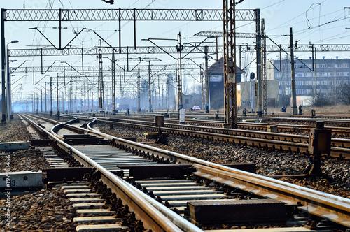 Foto Spatwand Spoorlijn Tory kolejowe, słupy i przewody zasilające na tle nieba.