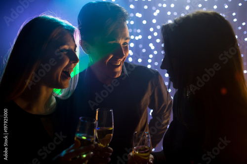 silhouette three young men and two women in hoods and with glass champagne celebrate a birthday have fun in a nightclub