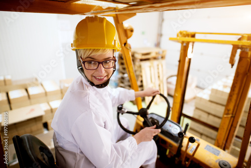 Fototapeta Young beautiful happy female worker is driving fork truck in reverse while carrying pallet with a stack of cardboard boxes.