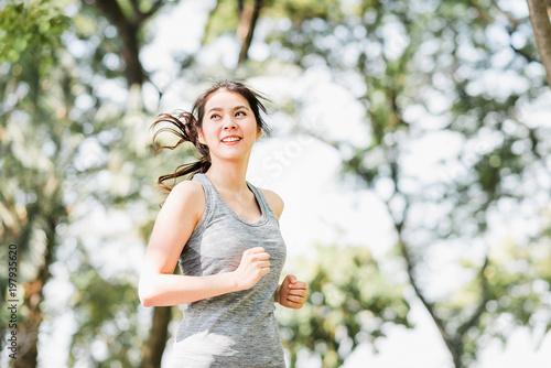 Fototapeta Healthy Asian woman running in the park