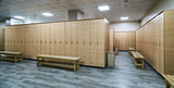 Wooden lockers with a wood bench in a locker room with doors closed. Locker room interior in modern fitness gym  - 197939451