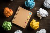 Notizbuch mit verschiedenen Farbmarkierungen und Papierkugeln auf Holzuntergrund