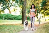 Fototapeta Sports woman walking with dog in the park.