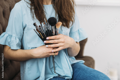 make up brushes in hands of beautiful young stylish woman